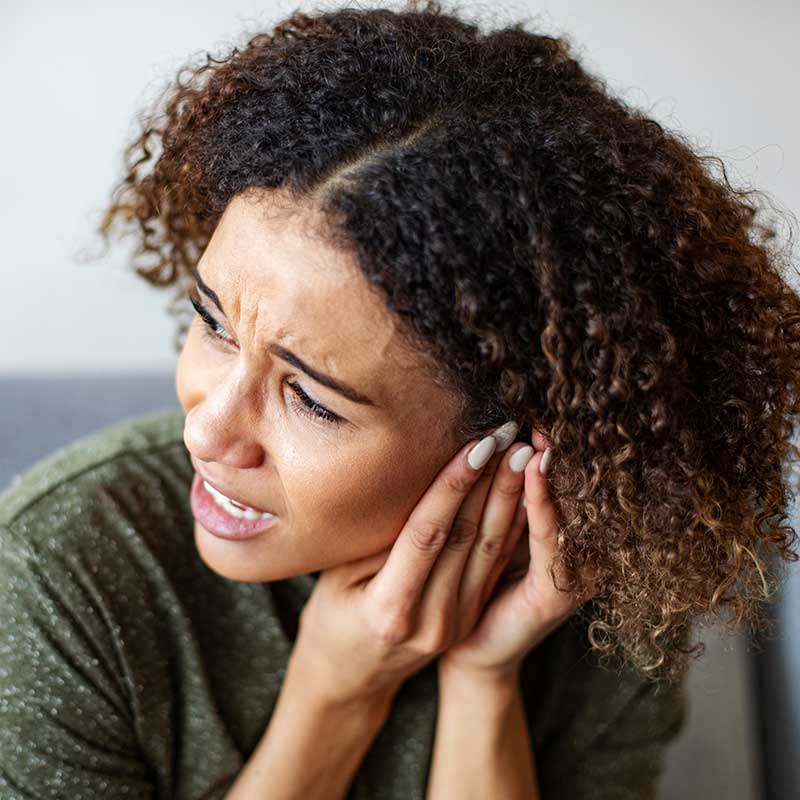 Woman pressing on ears to try to stop the ringing in her ears (tinnitus).