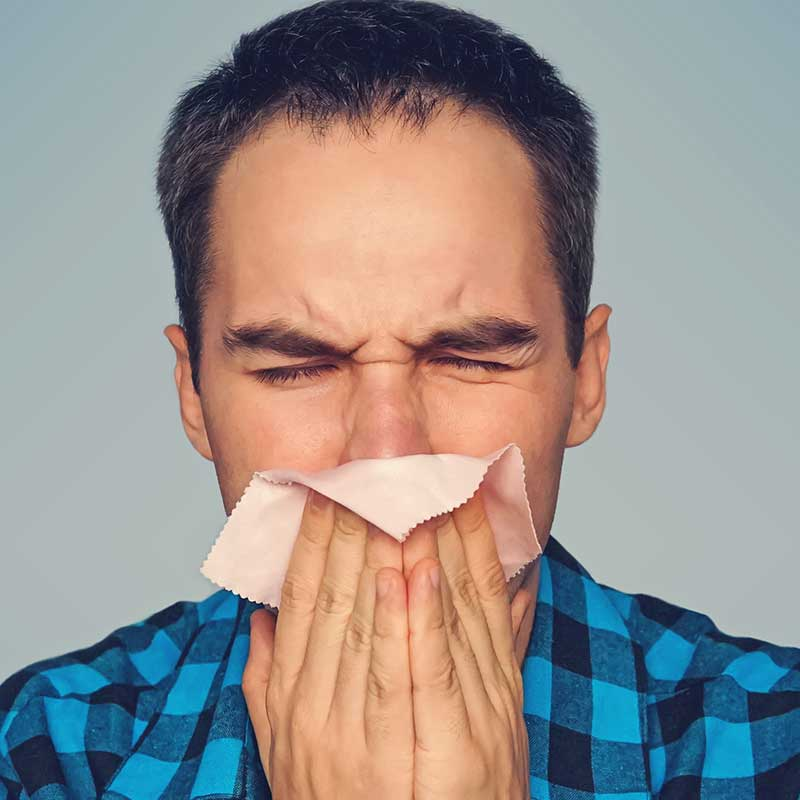 Man blowing nose in attempt to relive his allergies.